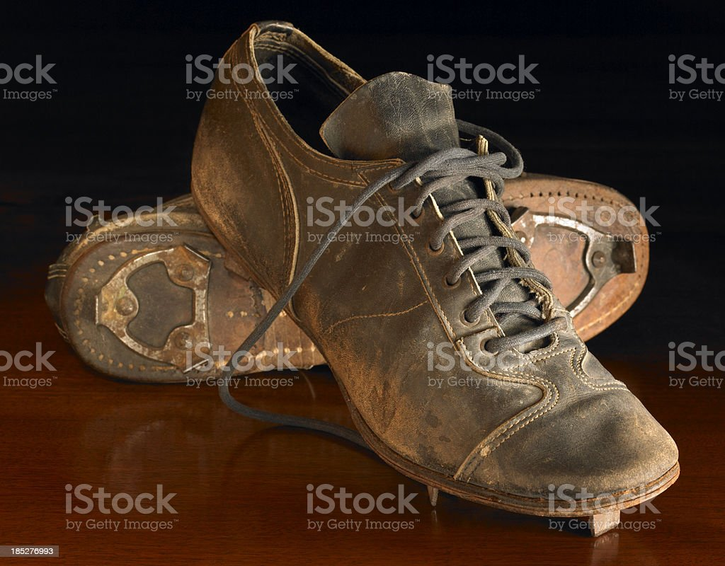 Antique baseball cleats on wood stock photo