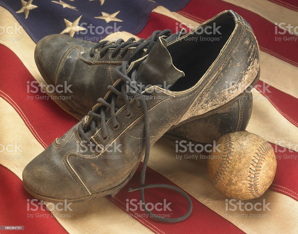 Antique baseball cleats with old-time ball on USA flag stock photo