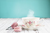 Antique Bavaria Winterling footed tea cup from the 1950's with pink macarons on a rustic white table against a teal background..