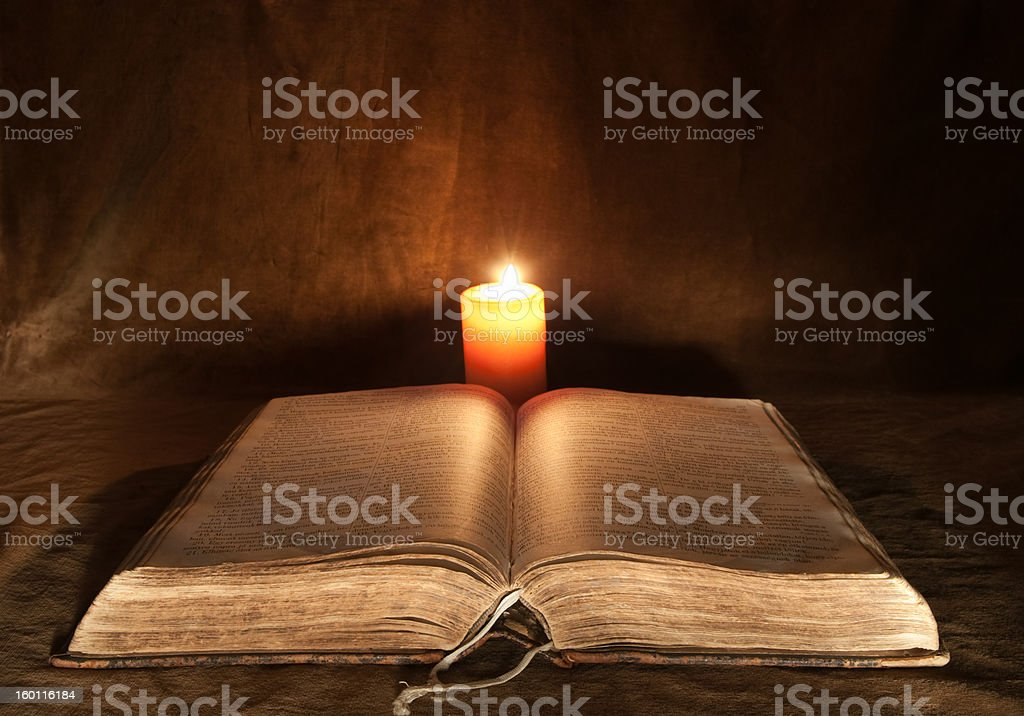 Antique Bible and candle. stock photo