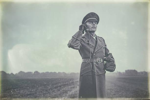Antiga foto preto e branco de oficial militar da década de 1940, chamando com telefone de campo em pé na terra. - foto de acervo
