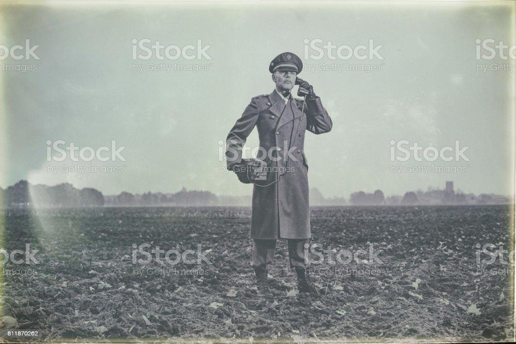 Antiga foto preto e branco de oficial militar da década de 1940, chamando com telefone de campo na fazenda. - foto de acervo