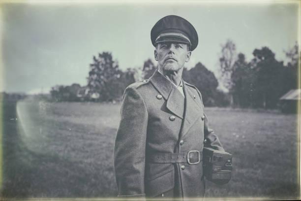 Foto preto e branco antiga da década de 1940 oficial militar permanente no campo com telefone. - foto de acervo