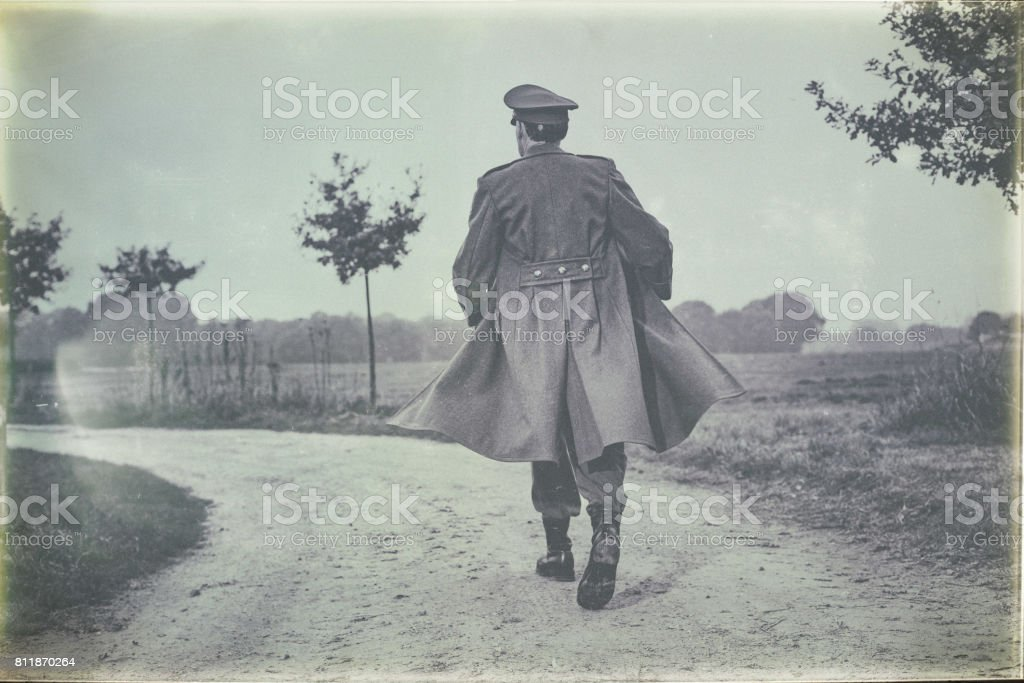Antique black and white photo of vintage 1940s military officer walking on  rural road. Rear