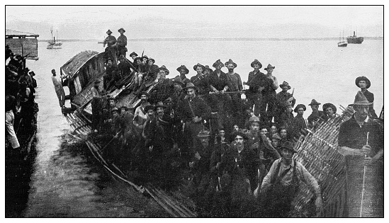 Antique black and white photograph of people from islands in the Caribbean and in the Pacific Ocean; Cuba, Hawaii, Philippines and others: American soldiers on Filipino boat