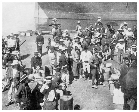 Antique black and white photograph of people from islands in the Caribbean and in the Pacific Ocean; Cuba, Hawaii, Philippines and others: Japanese contract laborers at Honolulu harbor, Hawaii