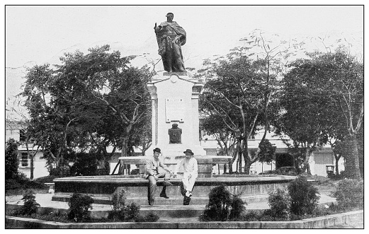 Antique black and white photograph of people from islands in the Caribbean and in the Pacific Ocean; Cuba, Hawaii, Philippines and others: Statue of Charles IV of Spain, Manila, Philippines