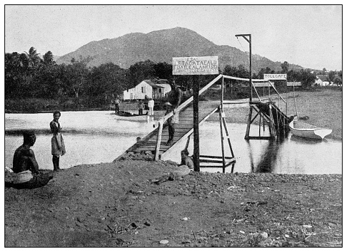 Antique black and white photograph of people from islands in the Caribbean and in the Pacific Ocean; Cuba, Hawaii, Philippines and others: Toll bridge near Apia, Samoa