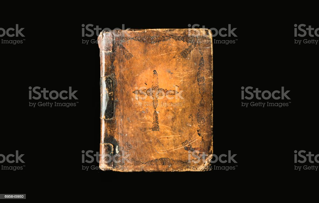 Antique book isolated on black background. Ancient Bible with cross on hard brown cover. Great book of Holy Scriptures bright on dark background. stock photo