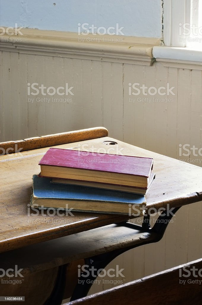 Antique Books Stacked on School Desk Dramatic Light stock photo