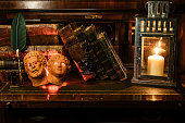 istock antique books stacked with a pocket watch. They're on a wooden desk on leather. It incorporates two masks of Roman gods and a pen with an inkwell 1254674747
