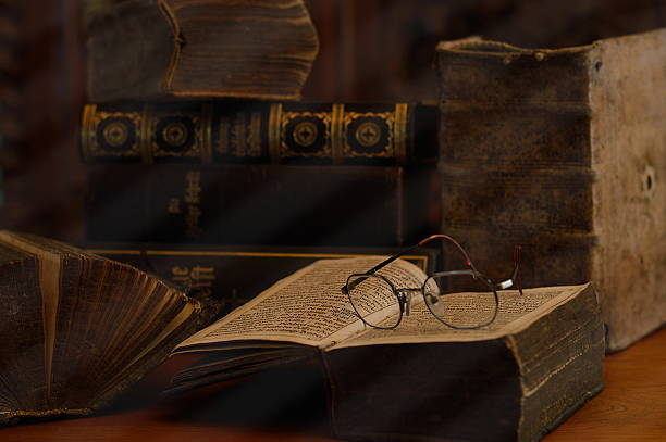 antique books with reading glasses in a dusty room - 歷史 個照片及圖片檔