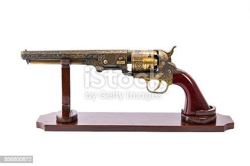 Antique brass gun with wooden stand on white background