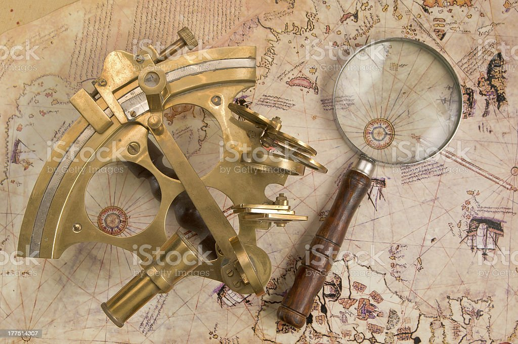 Antique brass sextant and magnifying glass over old Navigation Chart stock photo