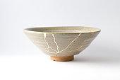 istock Antique broken Japanese beige bowl repaired with gold kintsugi technique 1280370446