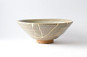 istock Antique broken Japanese beige bowl repaired with gold kintsugi technique 1280370446