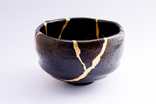 Antique broken Japanese black raku bowl repaired with gold kintsugi technique