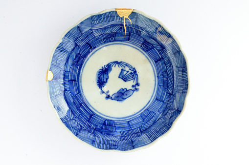 Kintsugi blue and white plate. Gold cracks restoration on old Japanese pottery restored with the antique Kintsugi restoration technique. The beauty of imperfections. japanese pottery repair gold. japanese art of repairing cracks with gold. japanese art of fixing broken pottery