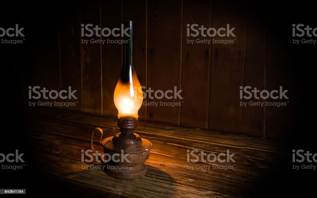 Antique burning paraffin lamp near on the wooden table. stock photo
