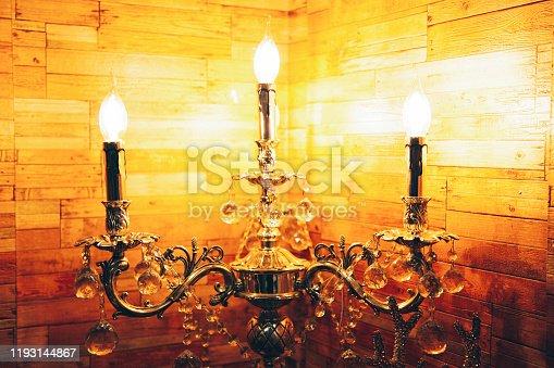 Antique candelabra with three melting candles on dark background