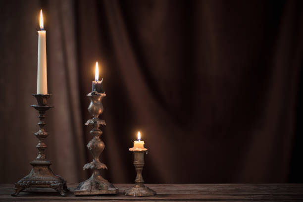 antique candlestick with burning candle on old wooden table on background brown velvet curtain stock photo