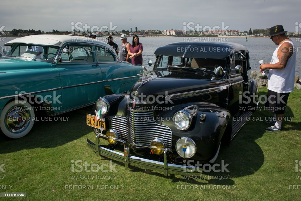 Horizontal shot of two antique cars, observed by a tattooed visitor,...