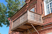 Antique carved wooden balcony on an old red brick building