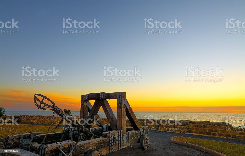 antique catapult by Alghero promenade at sunset stock photo