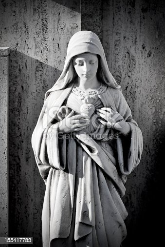 Antique cemetery statue close up: Virgin Mary heart.