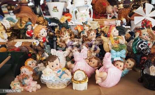 Antique porcelain dolls. Antique ceramic colorful hat trinkets sold in antique market