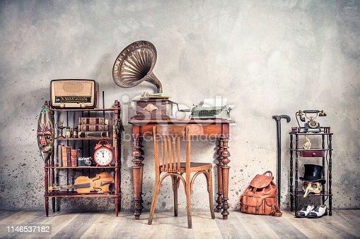 1065736660 istock photo Antique chair, old typewriter, retro radio,  gramophone on wooden desk, books, clock, camera, binoculars, fiddle, keys on shelf, mask, cylinder hat, shoes, cane, backpack. Vintage style filtered photo 1146537182