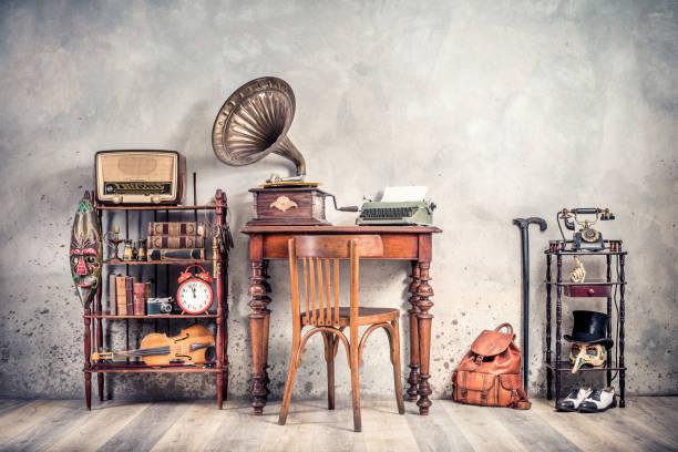 Antiquitätenstuhl, alte Schreibmaschine, Retro-Radio, Grammophon auf Holztisch, Bücher, Uhr, Kamera, Fernglas, Geige, Schlüssel im Regal, Maske, Zylindermütze, Schuhe, Stock, Rucksack. Vintage-Stil gefiltert Foto – Foto