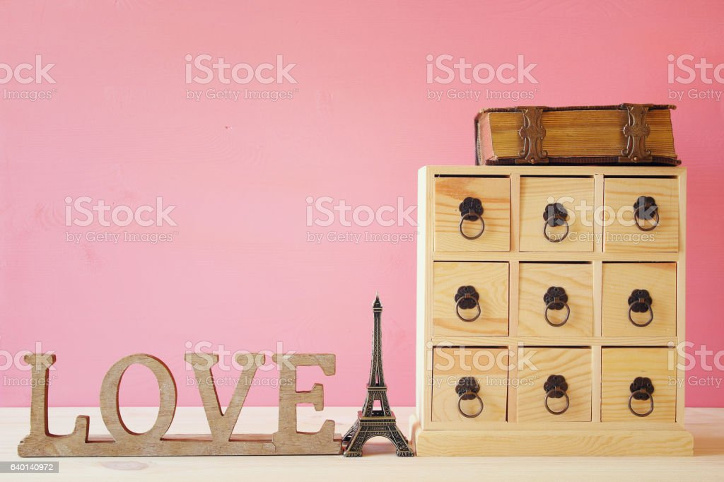 antique chest with drawers next to old book stock photo