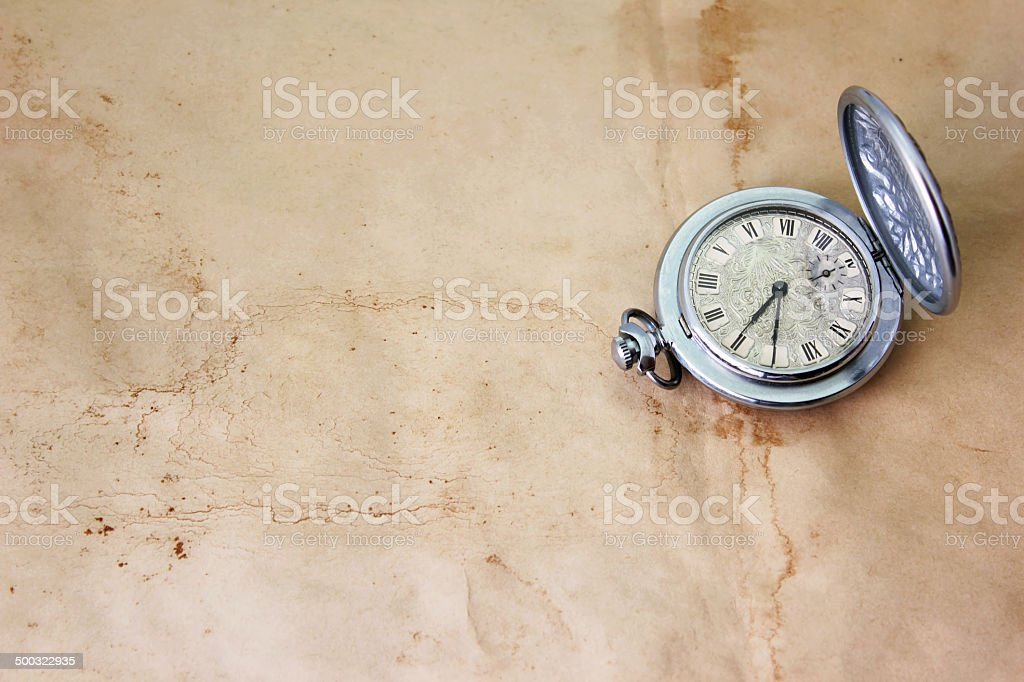 antique clock on the old dirty parchment stock photo