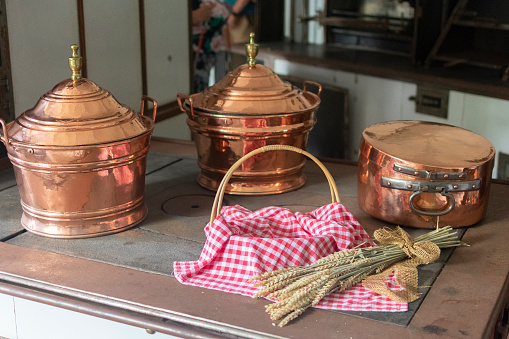 antique copper cookware on the stove