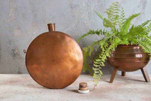Antique copper flask on concrete background. stock photo