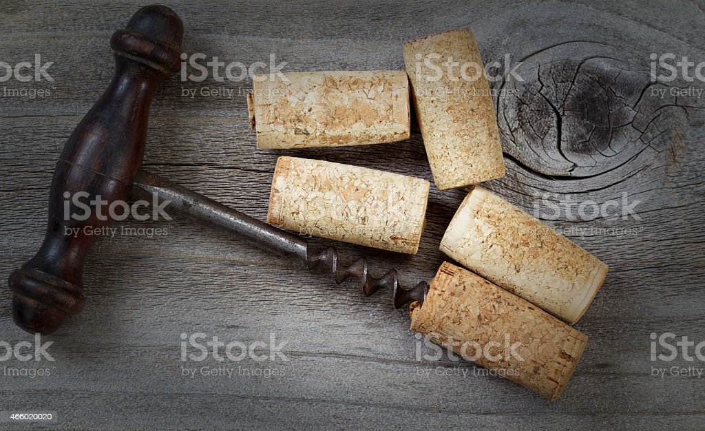 Antique corkscrew with used corks on aged wood stock photo