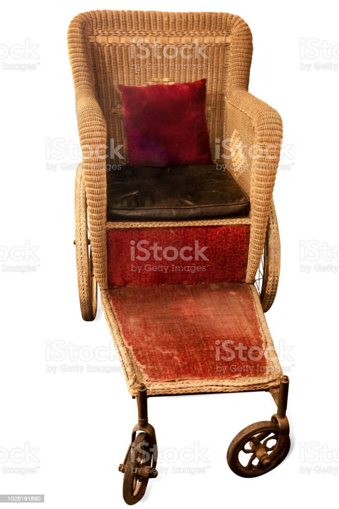 Antique courtesy wheelchair on white background with clipping path stock photo