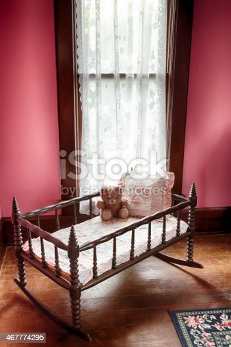 Antique Crib with teddy bear in room