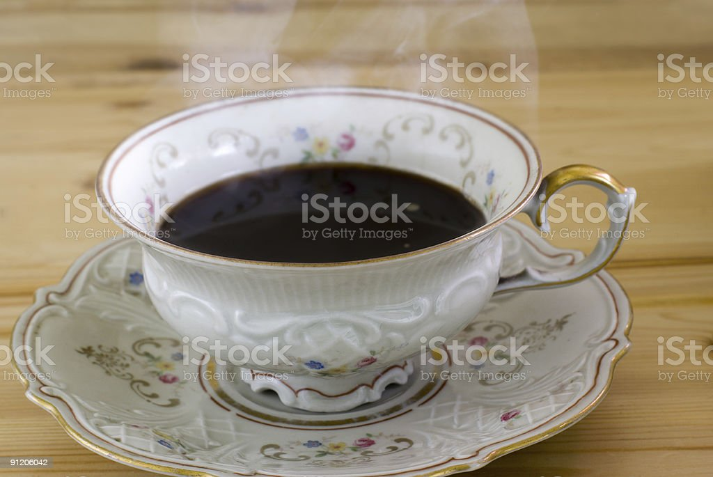 Antique cup with hot steaming coffee royalty-free stock photo