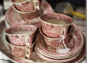 A collection of beautiful red and white antique dishes for sale is photographed.