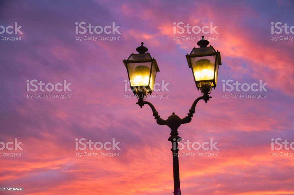 An antique street light with colorful evening clouds in the...