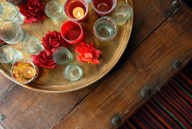Antique ethnic Indian coffee table with assorted glassware stock photo