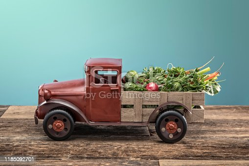 This is a old retro toy farm pick up truck with fresh produce including radishes, carrots, parsley, lettuce and brussel sprouts in the bed of the truck on a wood background. This image could work well as a concept for healthy take out food or organically grown vegan food.