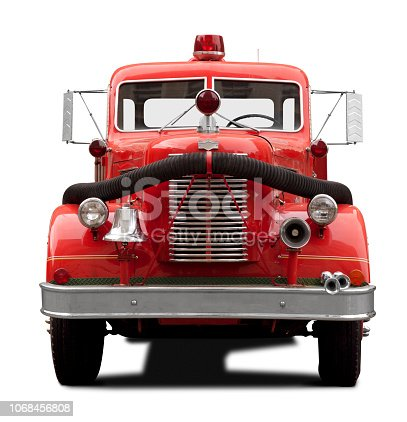 This is a front view of a old antique red fire truck facing the camera isolated on a white background. There is a drop shadow included with this photo