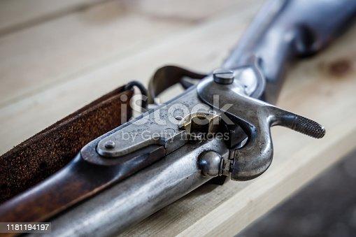 Antique flintlock gun lies on a wooden table
