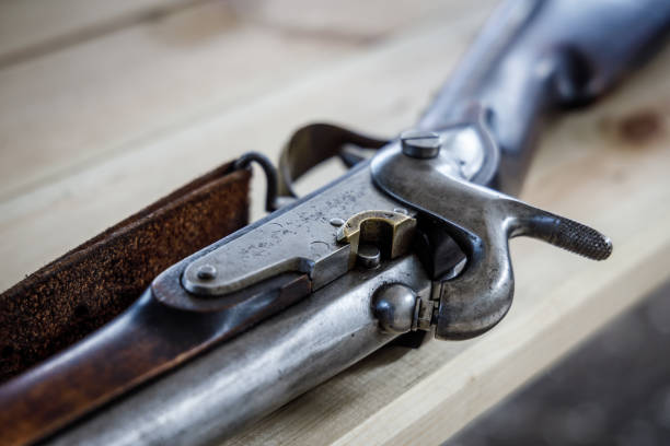 Antique flintlock gun lies on a wooden table stock photo