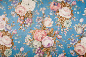 Antique floral fabric with clusters of pink, green and lavender flowers on a blue satin background..