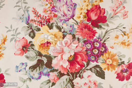 Antique floral fabric with clusters of pink, red, lavender, yellow and blue flowers on a beige background..
