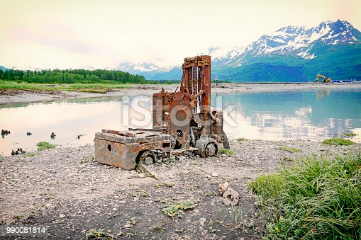 An antique forklift sits amongst the glorious beauty of Alaska's scenic landscape. Located beside the bay in Valdez, Alaska, this forklifts stands as a reminder of days gone by. This area marks the old townsite before the Great Earthquake of 1964.